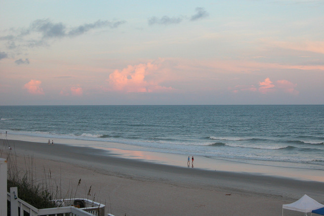 A few people meander down the beach in early morning.