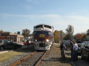 Train passing through Pine Mountain in front of bank.